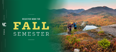 Photo of hikers on a mountain with fall foliage.