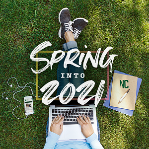 A student sitting on the grass holding a laptop computer, with the words Spring into 2021 across the picture.