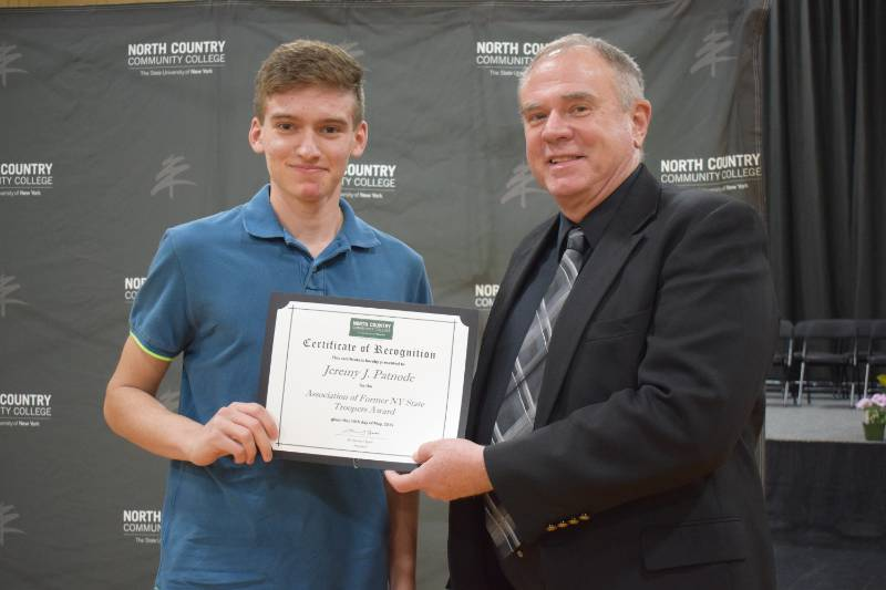 Jeremy Patnode of Chateaugay, named to the President's List for the Spring 2019 semester, receives an award from Criminal Justice program instructor Mike Saulpaugh.