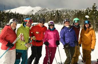 Skiers and snowboarders pose for a photo on the ski slopes at Whiteface Mountain