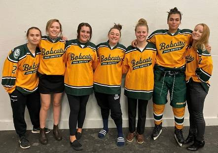 NCCC women's hockey players wearing their Paul Smith's jerseys standing side by side against a wall and smiling.