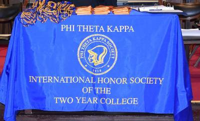 A blue Phi Theta Kappa banner with gold lettering draped over a table.
