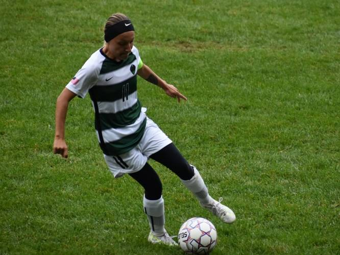 A soccer player with the ball at her feet on a field.